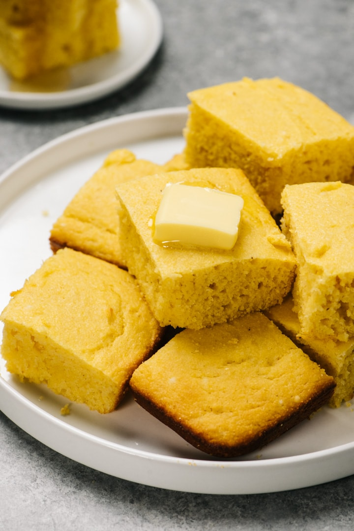 Healthy cornbread slices stacked on a platter on a cement background.