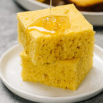 Two pieces of healthy cornbread stacked on a plate, drizzled with honey.