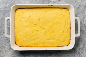Healthy baked cornbread in a rectangular casserole dish on a cement background.