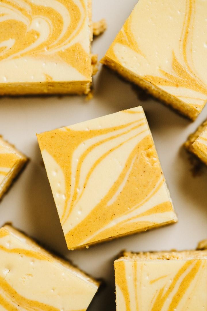 Pumpkin cheesecake bars on a tan background.