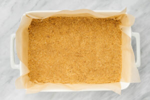 Graham cracker crust pressed into a parchment lined casserole dish.