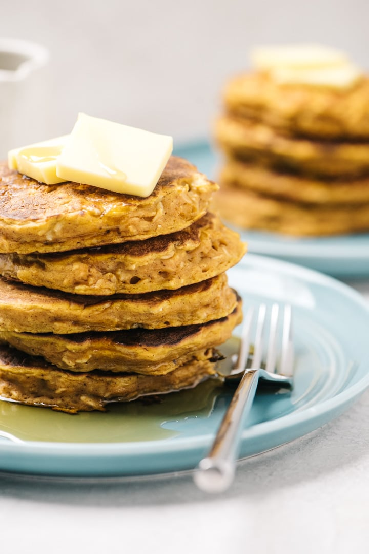Two blue plates with stacks of pumpkin oatmeal pancakes topped with butter.