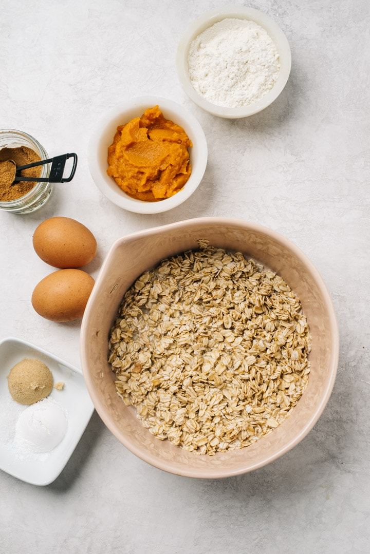 The ingredients for pumpkin oatmeal pancakes arranged on a cement background.