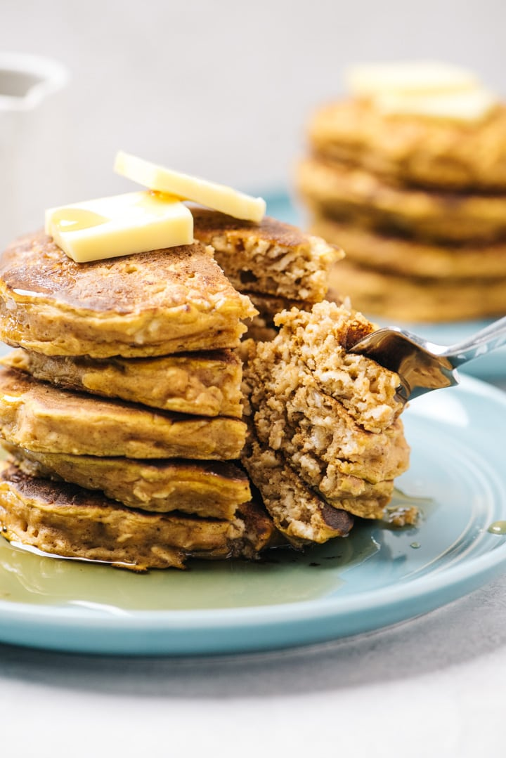 A fork removing a bite from a stack of pumpkin oatmeal pancakes.