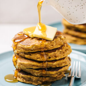 Pouring maple syrup over a stack of pumpkin oatmeal pancakes on a blue plate.
