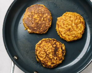 Pumpkin pancakes with oatmeal cooking in a skillet.