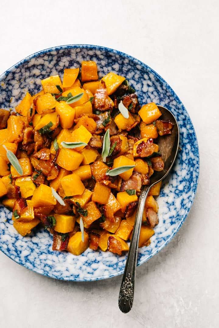 Roasted butternut squash with bacon and fresh sage in a blue speckled serving bowl on a cement background with a silver vintage serving spoon.