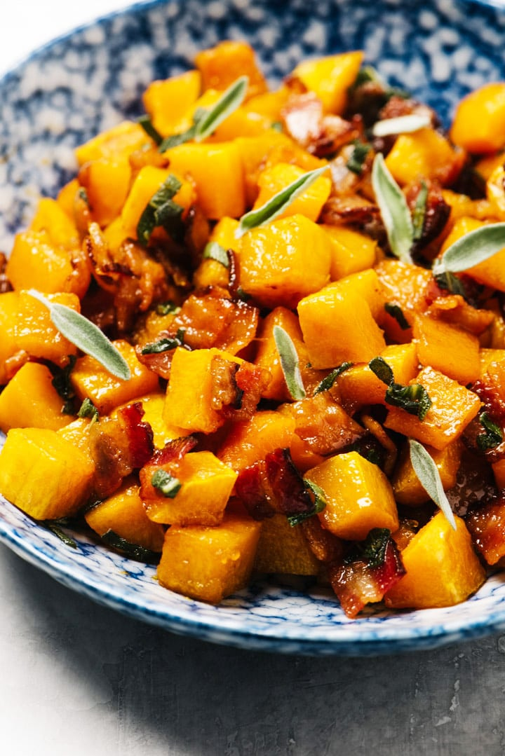 Side view, a blue speckled serving bowl filled with roasted butternut squash, bacon, and fresh sage.