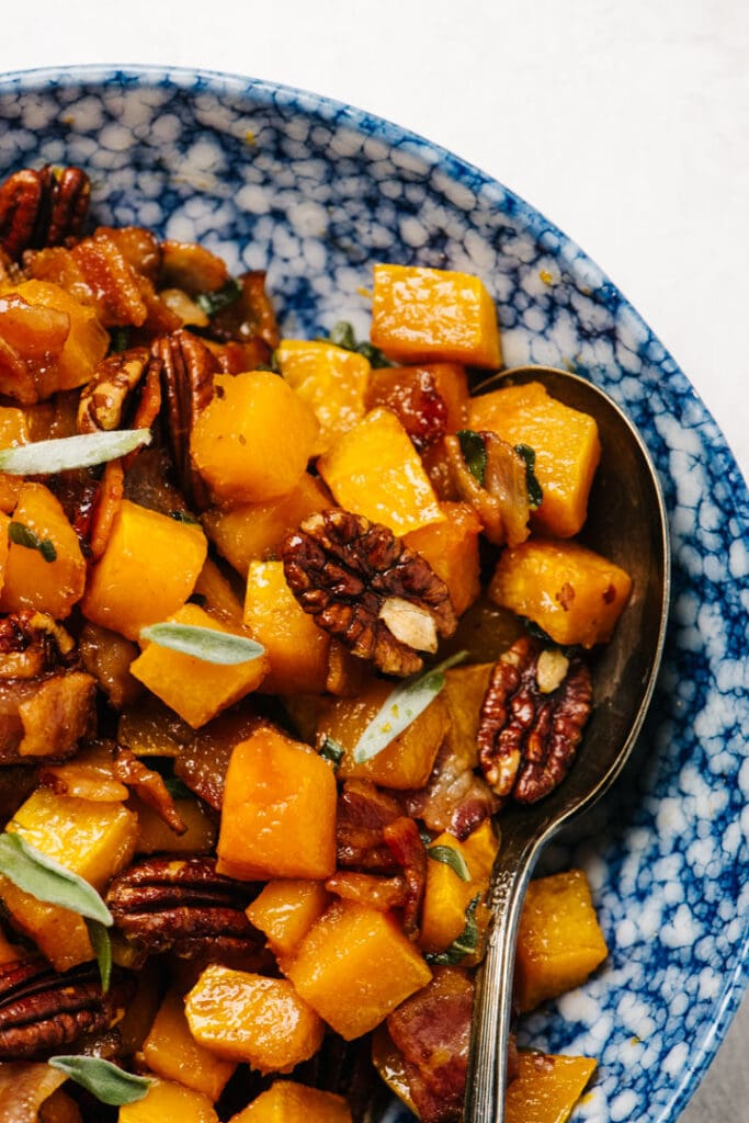 Roasted butternut squash with bacon and peans in a blue speckled bowl with a vintage serving spoon.