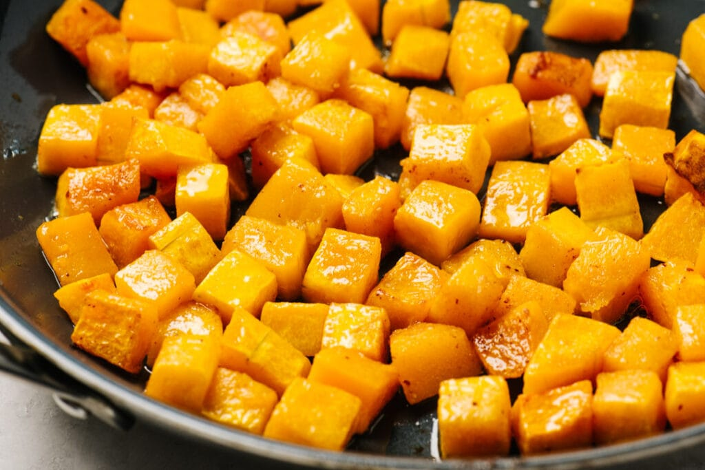 Roasted butternut squash cubes tossed with bacon fat in a skillet.