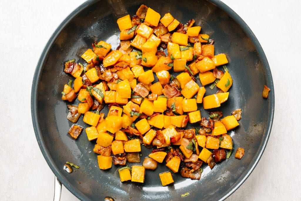 Roasted butternut squash with diced cooked bacon in a skillet.