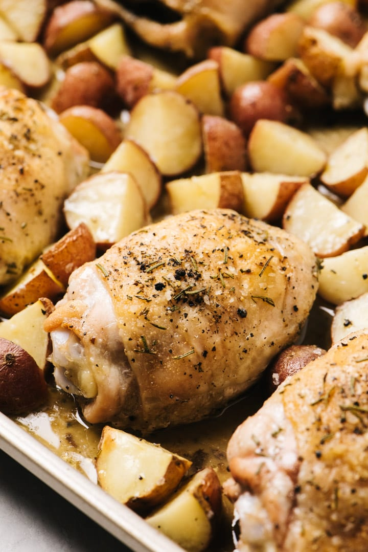 Side view, rosemary chicken with potatoes on a sheet pan fresh from the oven.