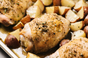 Side view, rosemary chicken on a sheet pan with quartered red potatoes.