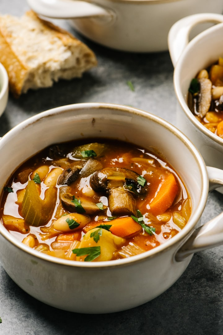 Several crocks of vegetable stew on a cement background with pieces of bread scattered around the bowls.