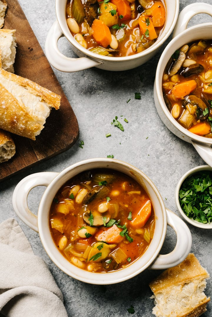 Three bowls of white bean vegetable stew on a cement background with slices of bread on a cutting board to the side and a tan linen napkin.