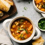 Several bowls of vegan stew on a cement background with slices of bread on a cutting board to the side and a tan linen napkin.
