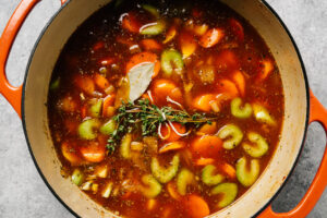 Vegetables simmering in a savory stew gravy topped with fresh thyme and a bay leaf.