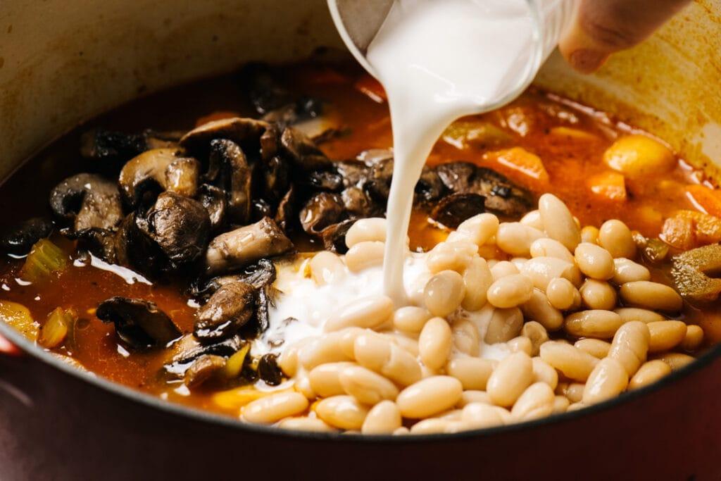 Adding a cornstarch slurry to a pot of vegan stew.