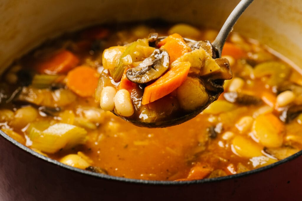 A ladle full of vegan stew hovering over a dutch oven.
