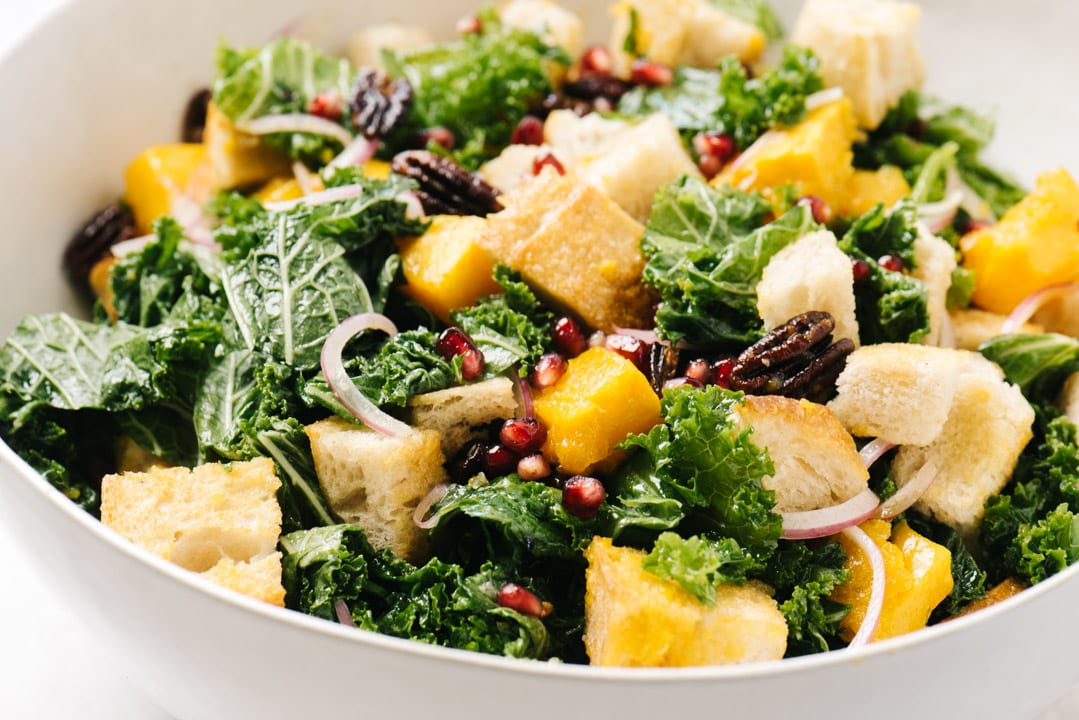 Side view, a large white salad bowl filled with butternut squash panzanella salad.