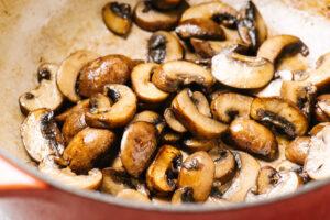 Sautéed crimini mushrooms in a red dutch oven.