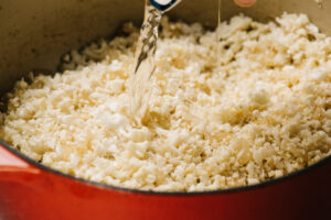 Pouring white wine into partially cooked cauliflower rice with onions.