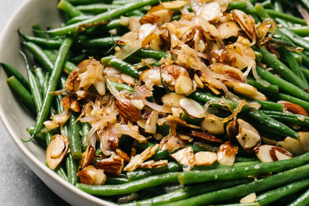 Side view, green beans almondine in a tan serving bowl.