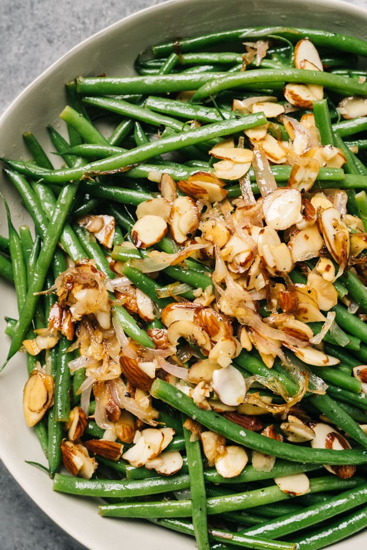 A tan serving bowl of green beans almondine on a concrete background.