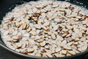 Silvered almonds sauteeing in butter in a skillet.