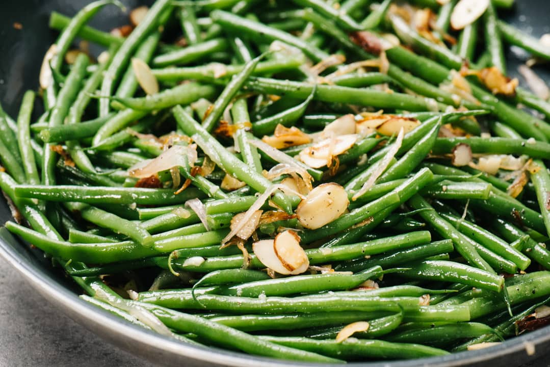 Tossing green beans with sauteed almond and shallots in a skillet.