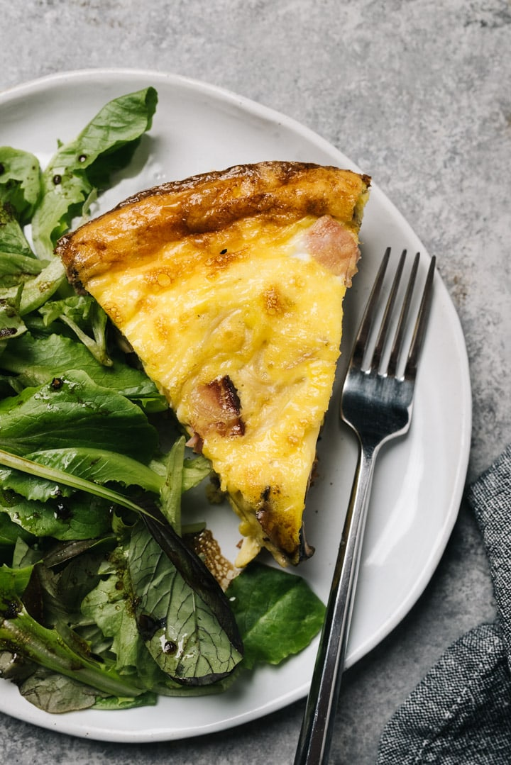 A slice of ham frittata on a white plate with a tossed green salad and silver fork.