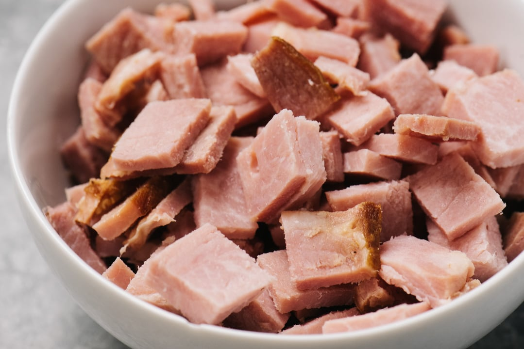 Chopped leftover ham in a small white bowl.
