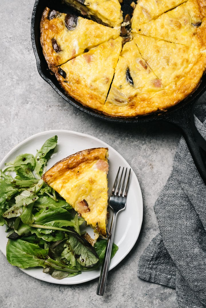 A slice of ham frittata on a white plate with a tossed green salad and a ham quiche in a cast iron skillet on a concrete background.