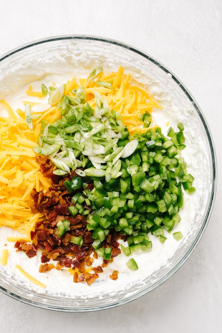 A bowl of whipped cream cheese and sour cream with cooked bacon, shredded cheese, minced jalapenos, and sliced green onions on top.