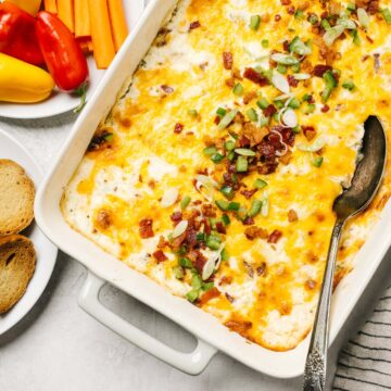 Jalapeno popper dip in a casserole dish on a concrete background surrounded by plates of bread slices and raw vegetables.