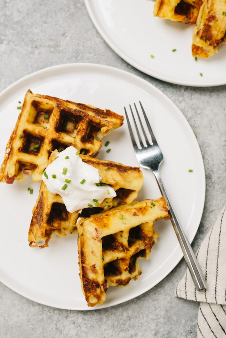 Three mashed potato waffles lined up on a white plate with a dollop of sour cream, silver fork, and striped linen to the side.