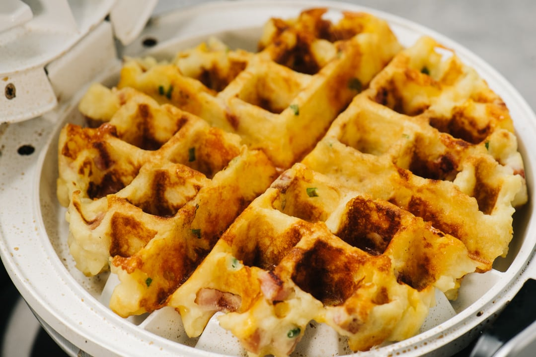 A mashed potato waffle with bacon and chives in a waffle iron.