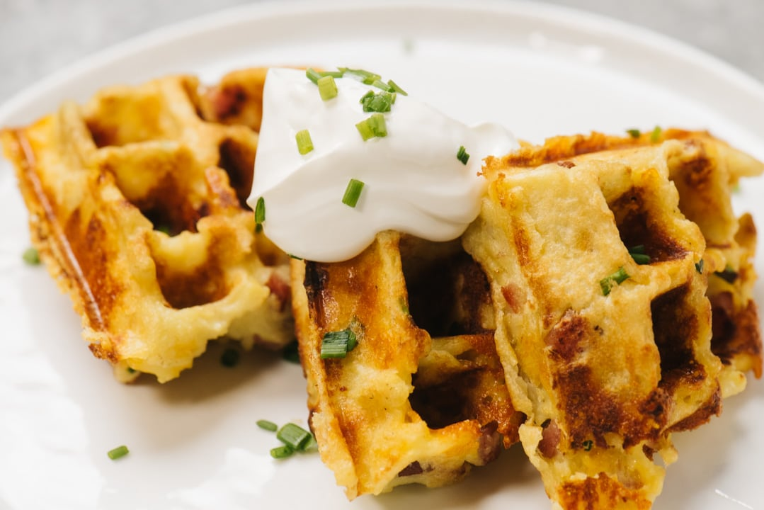 Three mashed potato waffles arranged on a white plate dolloped with whipped cream