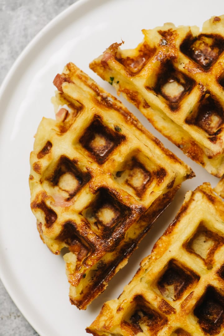 Overhead view of a mashed potato waffle divided into four pieces on a white plate.