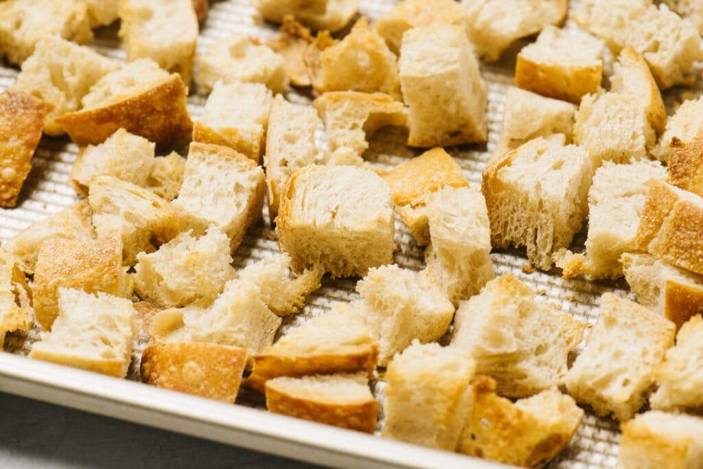 Golden brown sourdough cubes on a baking sheet.