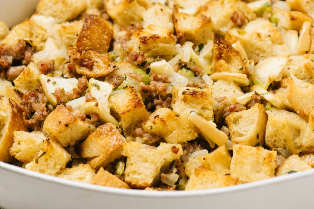 Side view, golden brown sausage stuffing in a white casserole dish, fresh from the oven.