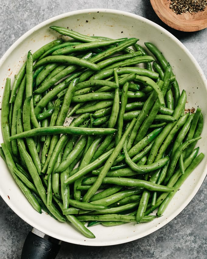 Raw green beans tossed with rendered bacon fat and pepper in a skillet.