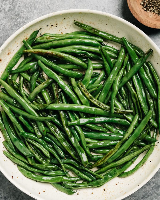 Charred sautéed green beans in a skillet.