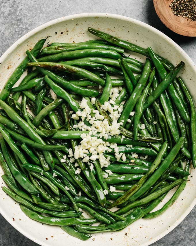 Charred sautéed green beans in a skillet with minced garlic.