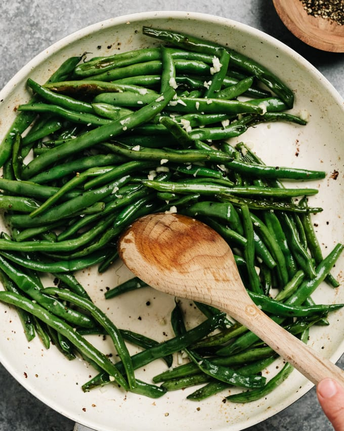 Sautéing green beans with minced bacon.