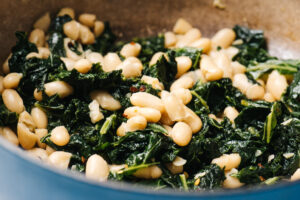Side view, beans and greens in a blue dutch oven.