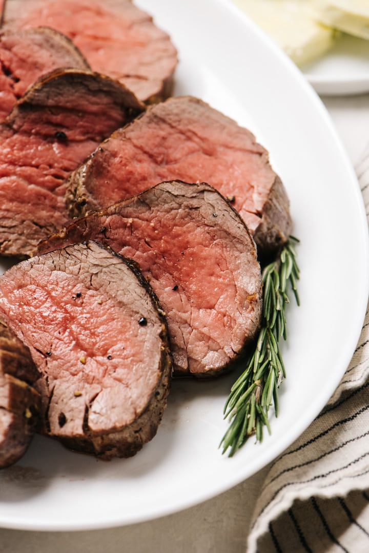 """Slices of beef tenderloin sliced into ½"""" pieces and arranged on a white platter with a sprig of rosemary."""