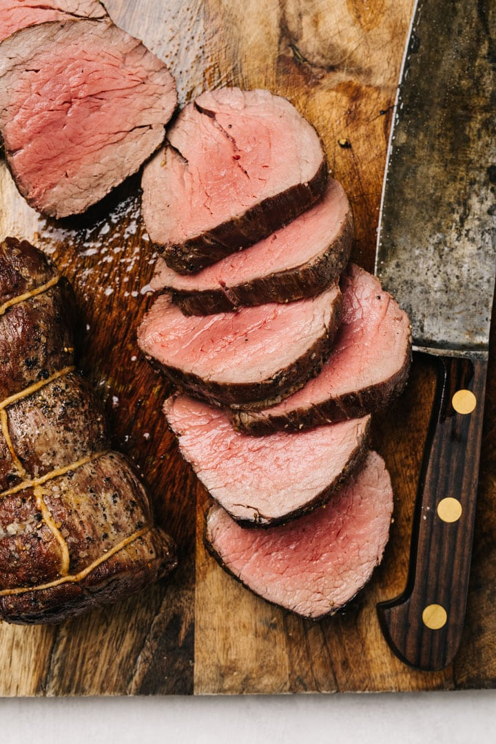 A whole beef tenderloin resting on a cutting board next to carved slices of tenderloin with a cutting knife.