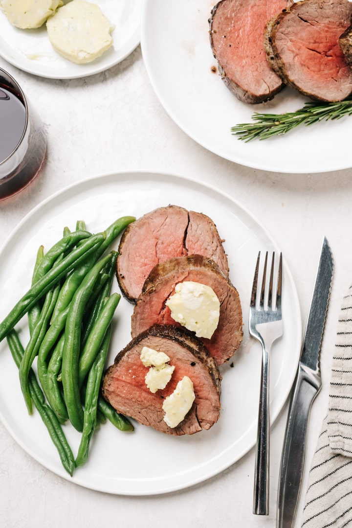 Three slices of beef tenderloin topped with blue cheese butter and served with green beans on a white plate with a silver knife and fork, glass of red wine, and striped linen napkin.