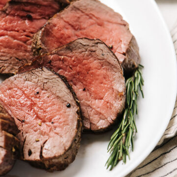 "Slices of beef tenderloin sliced into 1/2"" pieces and arranged on a white platter with a sprig of rosemary."
